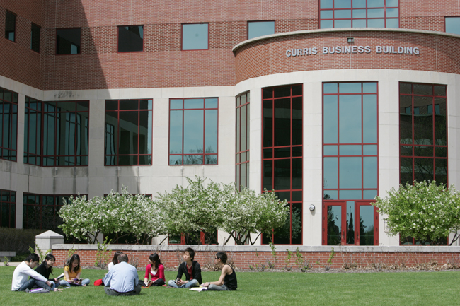Students sitting together outside of Curris Business Building